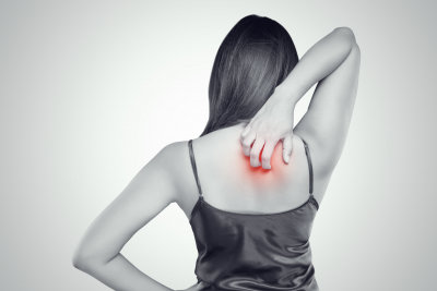 Woman scratching her itchy back with allergy rash,